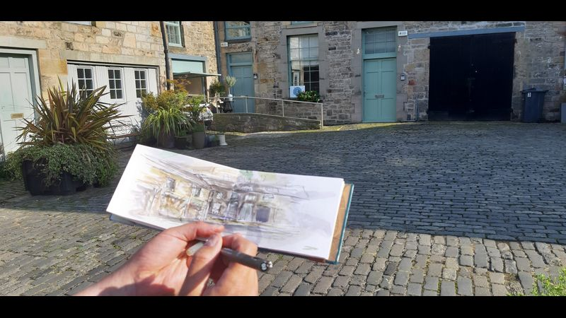 Mark Kirkham sketching plants in his hand bound sketchbook in The Arienas Collective courtyard.