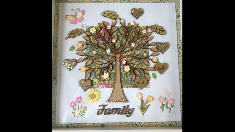 A Personalised family tree in a colour theme of Gold. Embellished with wooden glitter hearts and paper flowers. Handwritten names. Wooden word of Family.