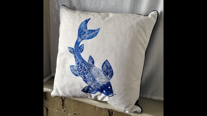 Front view of the blue hand-printed koi fish cushion.