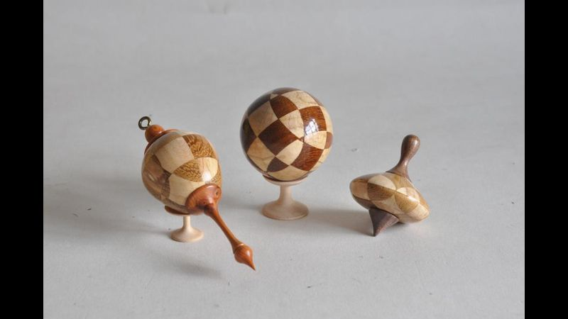 a trio of yots including a spinning top a ball and an ornament