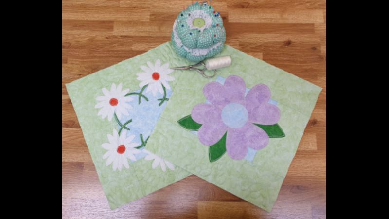 Two appliqué designs on table.  The Flower block will be demonstrated in class