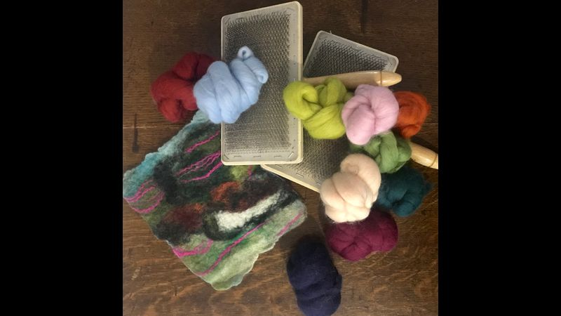 A pile of merino wool tops, hand held carders on top of a small wet felted abstract landscape