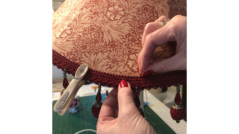 Tailor stitching trimming onto an handmade tailored lampshade in Morris