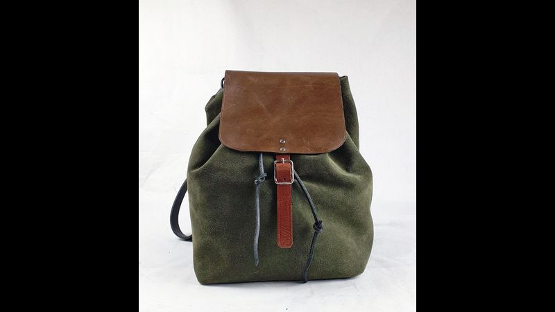 Bag in a Day backpack course. Front view of the backpack in green suede with grey vegetable tanned leather flap, tan leather details and silver hardware