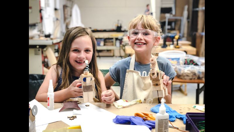 Two girls proudly show off their wooden characters built at an Ash & Co. Workshops mini-maker woodworking session for kids