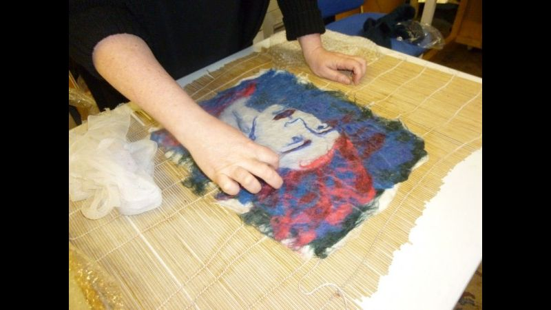 Student adding details to her felt portrait in a beginners feltmaking course in the Forest of Dean.