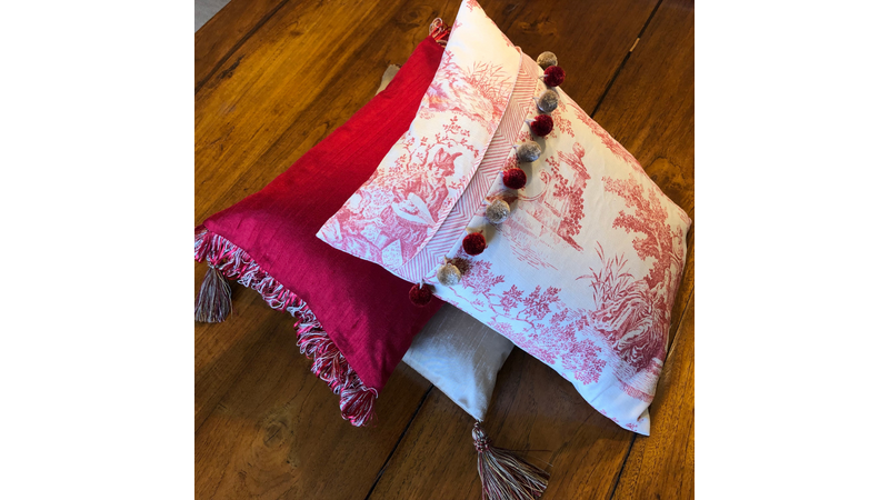 Bespoke scatter cushions in hues of red and cream with pom pom and ribbon trim