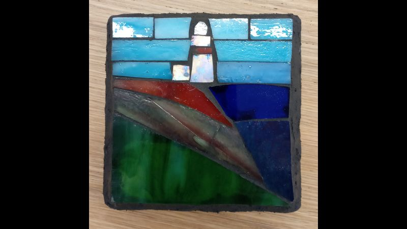 Stained glass lighthouse on slate.