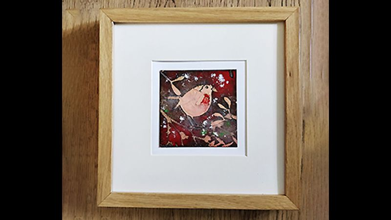 An enamelled Christmas creation mounted within a frame