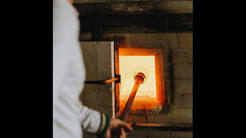 Gather hot glass from the furnace