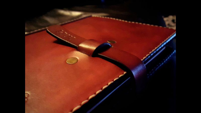 Red book with closure flap and initials stamped