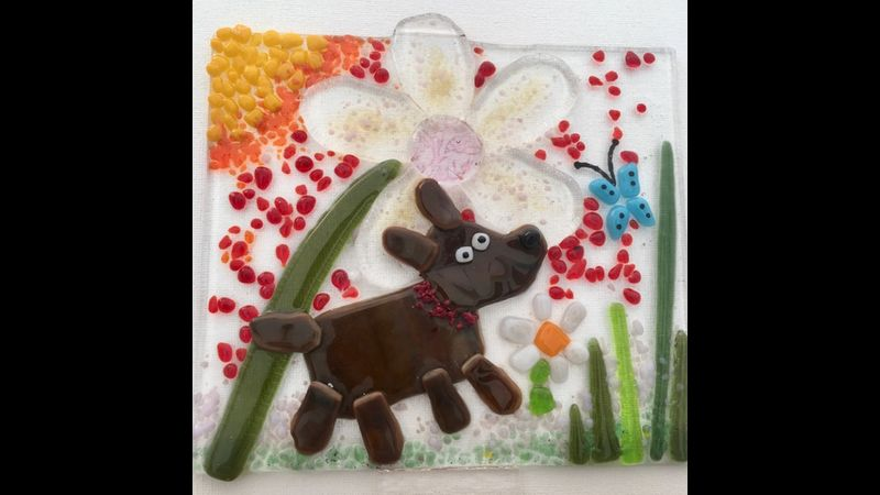 This is a fused glass panel created by a participant at the 'Kitty's and Puppies' Evening of 'Glass Fusing' workshop. Dimensions are  15cm square. Guests may choose to apply glass hooks so that it may be hung from a window, or not as it can also be displayed in a box frame.