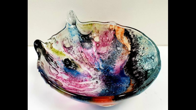 A Fused Glass slump bowl inspired by the Northern Lights, made by Melanie the workshop facilitator.