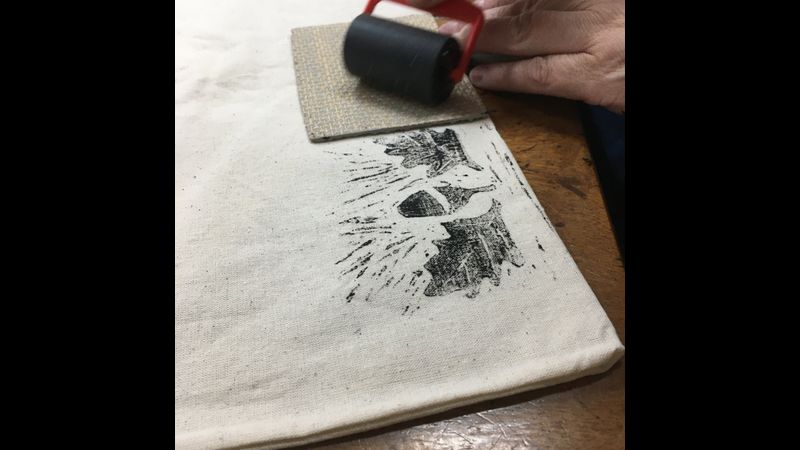 student printing with a lino they have made in a printmaking workshop