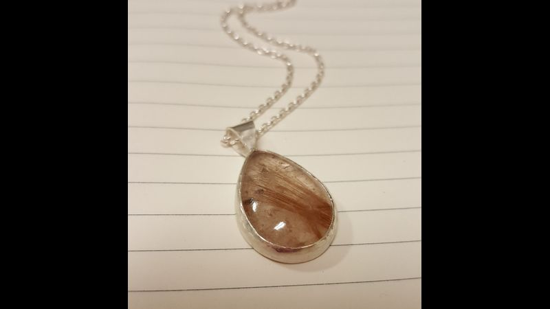 rutilated quartz in an open backed bezel setting with shaped bail